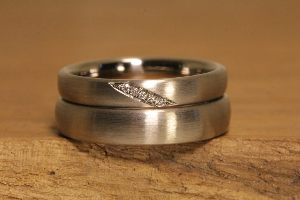 Image 014a: single-colored wedding rings in gray gold, matt with diamonds.