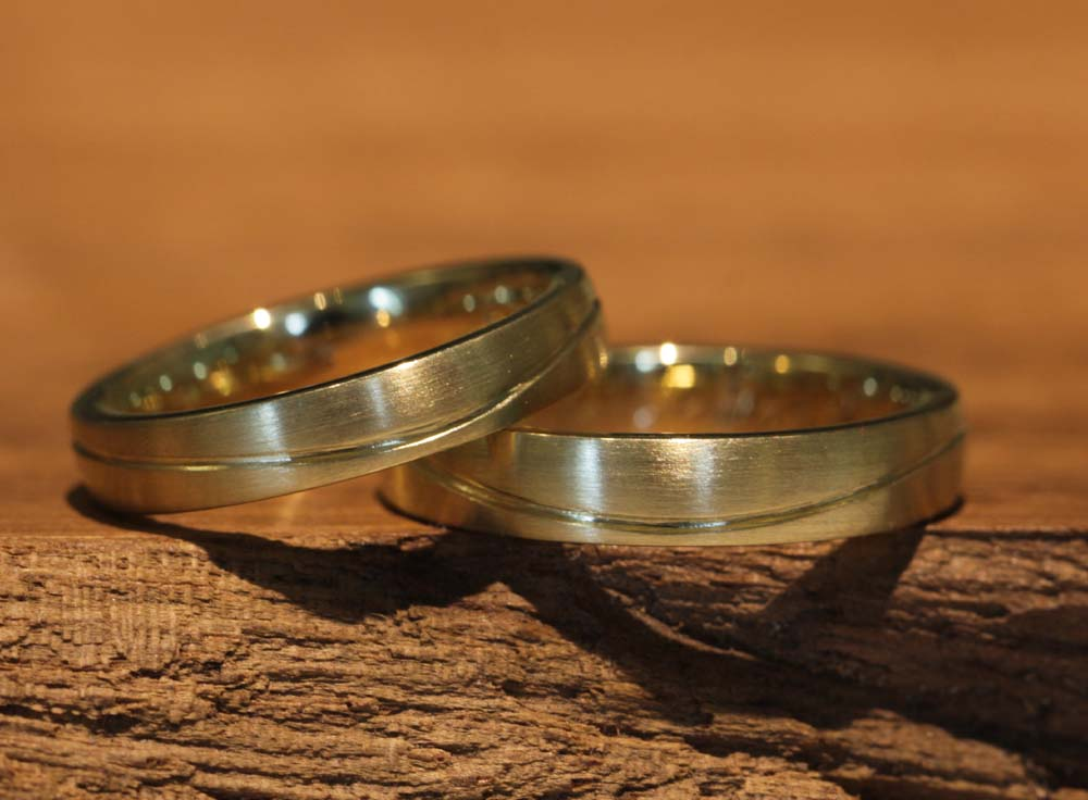 Image 029: Unique wedding rings in yellow gold with a wavy line, forged in-house.