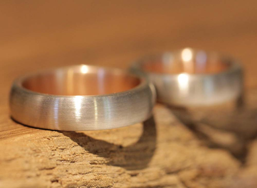 Image 033a: thick wedding rings, bicolor, red gold inside, gray gold outside.