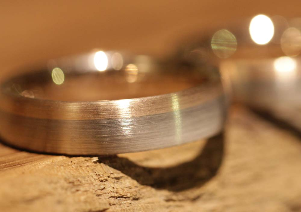 Image 035: two-tone wedding rings with a transition from gray gold to rose gold.