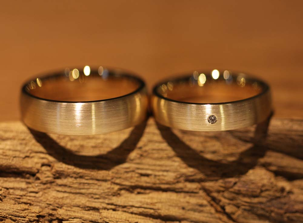 Image 040: wide, single-colored wedding rings with stone, rose gold, matt outside, shiny inside.