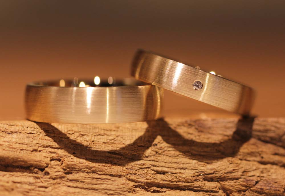 Image 040a: wide, single-colored wedding rings with diamond, rose gold.