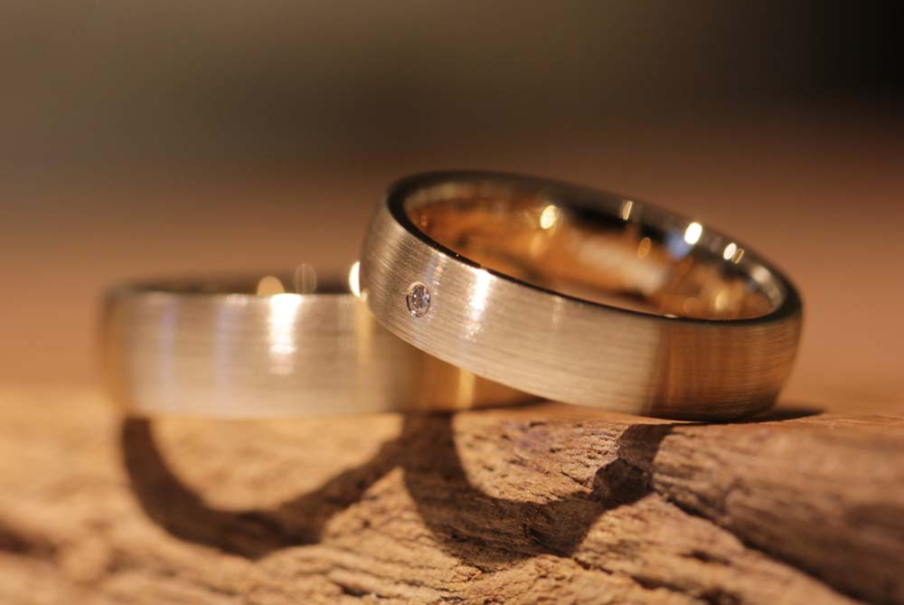 Image 040b: wide, simple wedding rings with diamond, rose gold, matt outside.