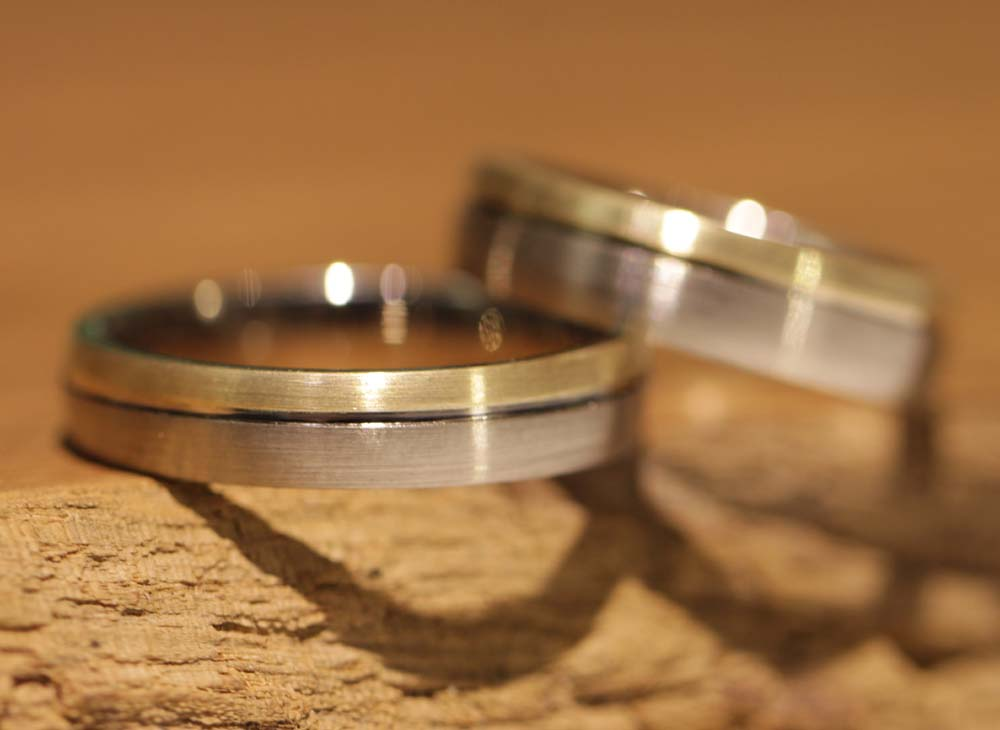 Image 044: bicolor wedding rings, hand-forged in the course, gray gold with yellow gold and milled line.