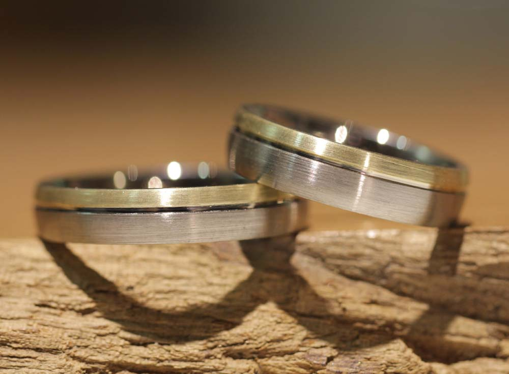 Image 044a: bicolor wedding rings, hand-forged in the course, gray gold with yellow gold and milled line.