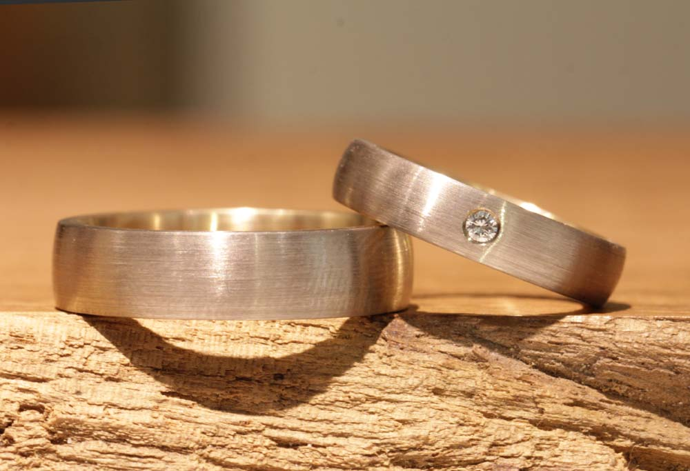 Image 047a: two-tone wedding rings with stone, forged in the wedding ring course.