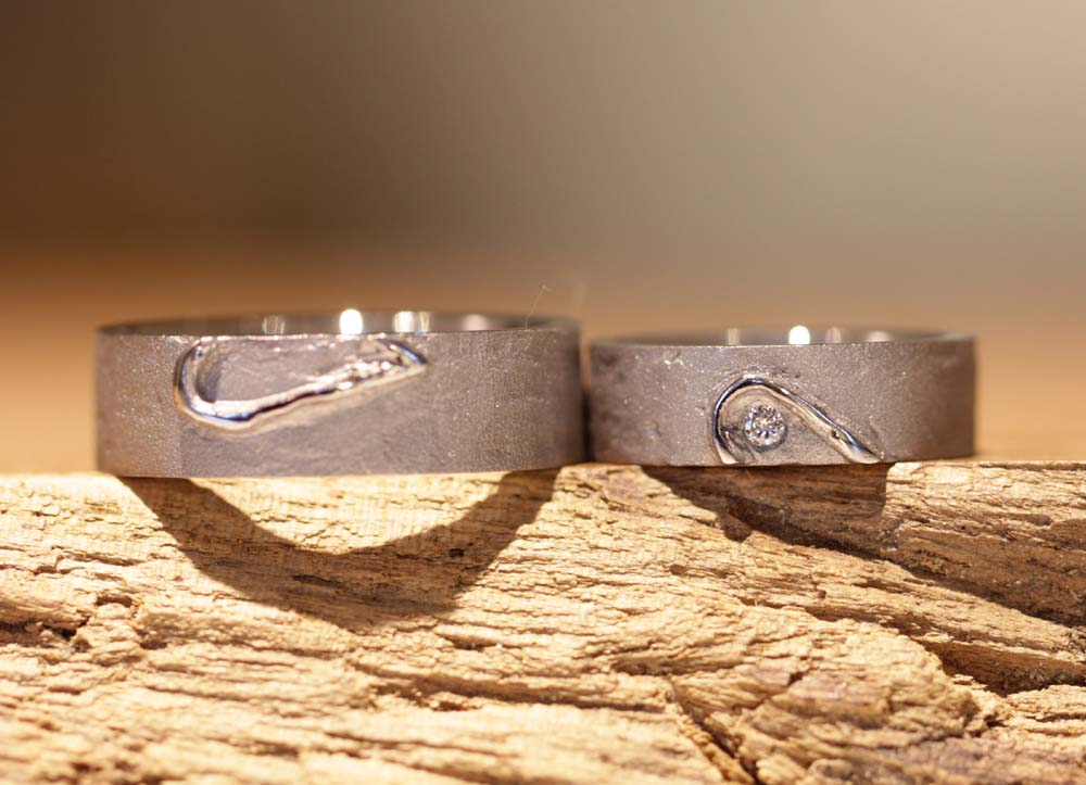 Image 066: Rustic wedding rings with a split heart and diamond.