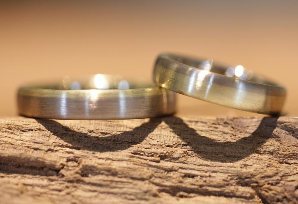 Image 155a: two-tone wedding rings, gray and yellow gold, each positioned in reverse.
