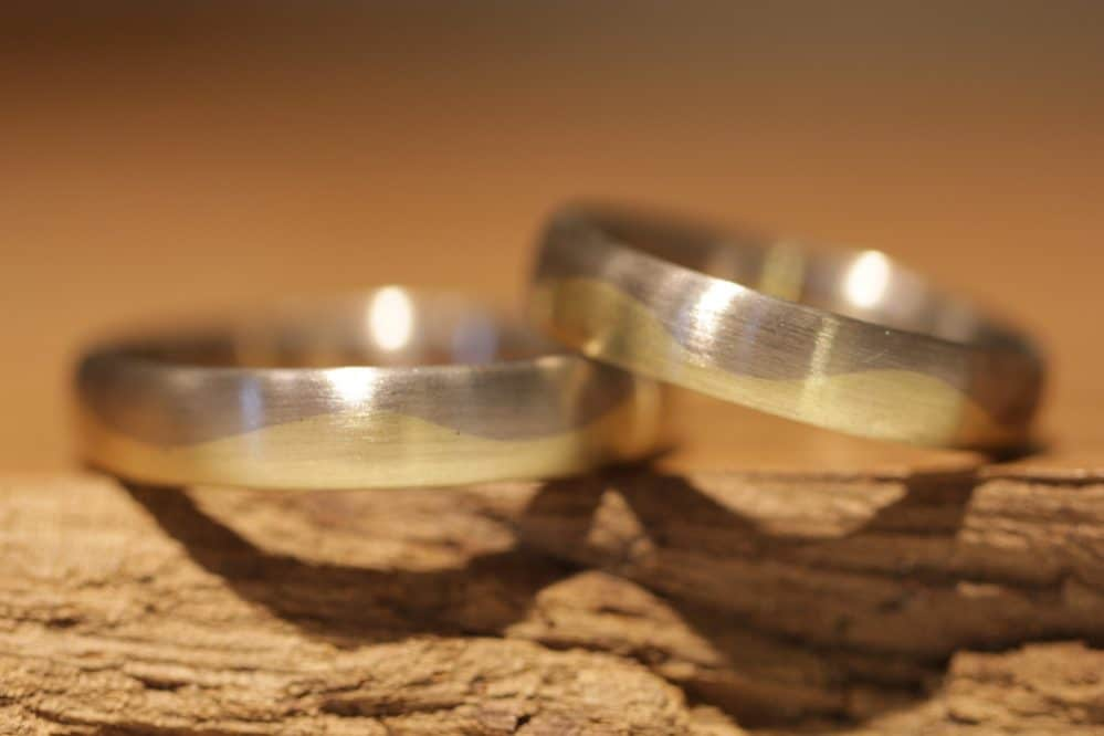 Image 160b: Wedding rings made of gray and yellow gold with a wave pattern.
