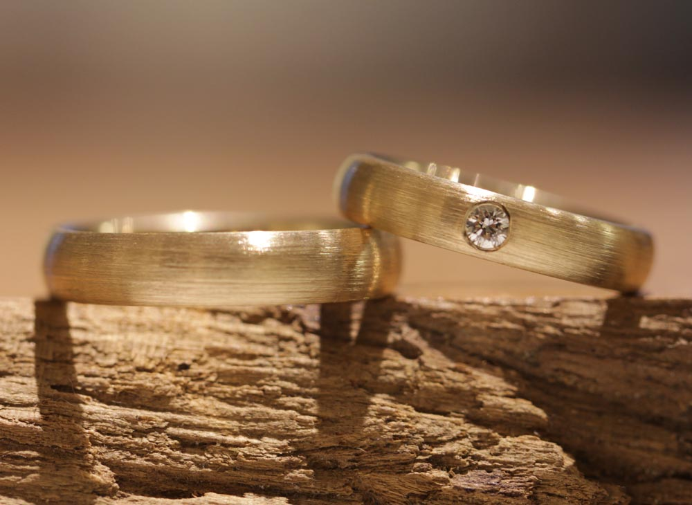 Image 165a: classic wedding rings made of yellow gold with a matt surface, a diamond in the ladies' ring.