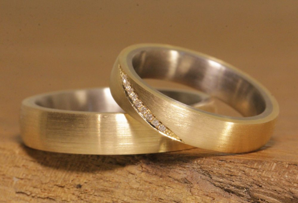 Image 173a: two-tone wedding rings using the soldering technique, angled line with diamonds in the women's ring.