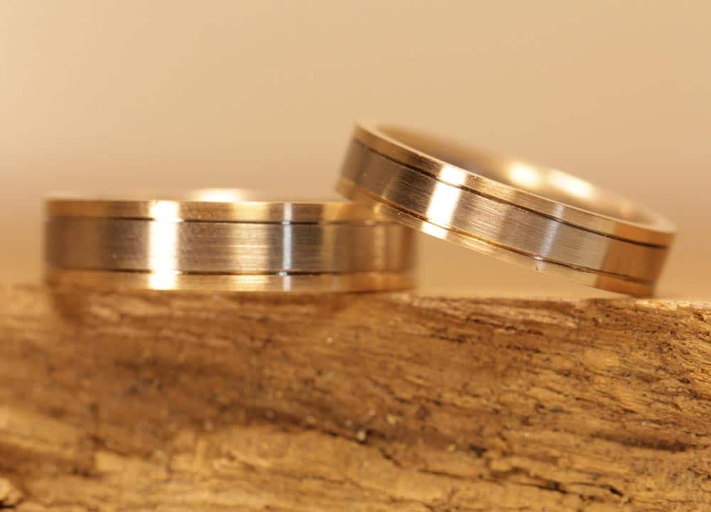 Image 176a: multicolored wedding rings with line, red gold and gray gold, matt.