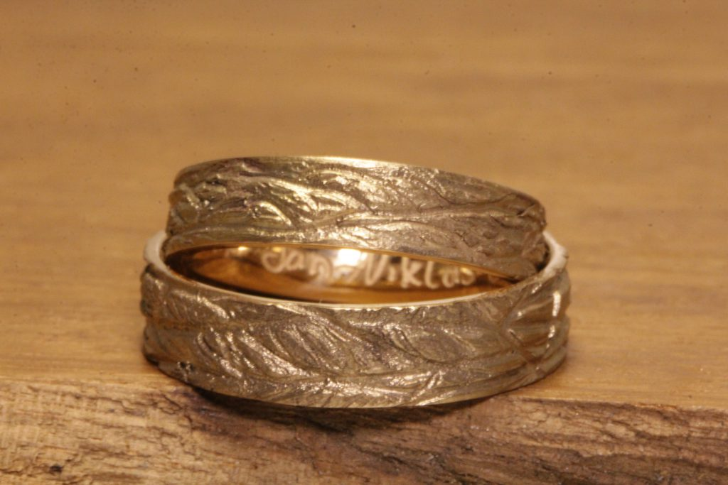 Image 191: Pair of wedding rings made of rose gold, polished and engraved on the inside, cast structure on the outside.
